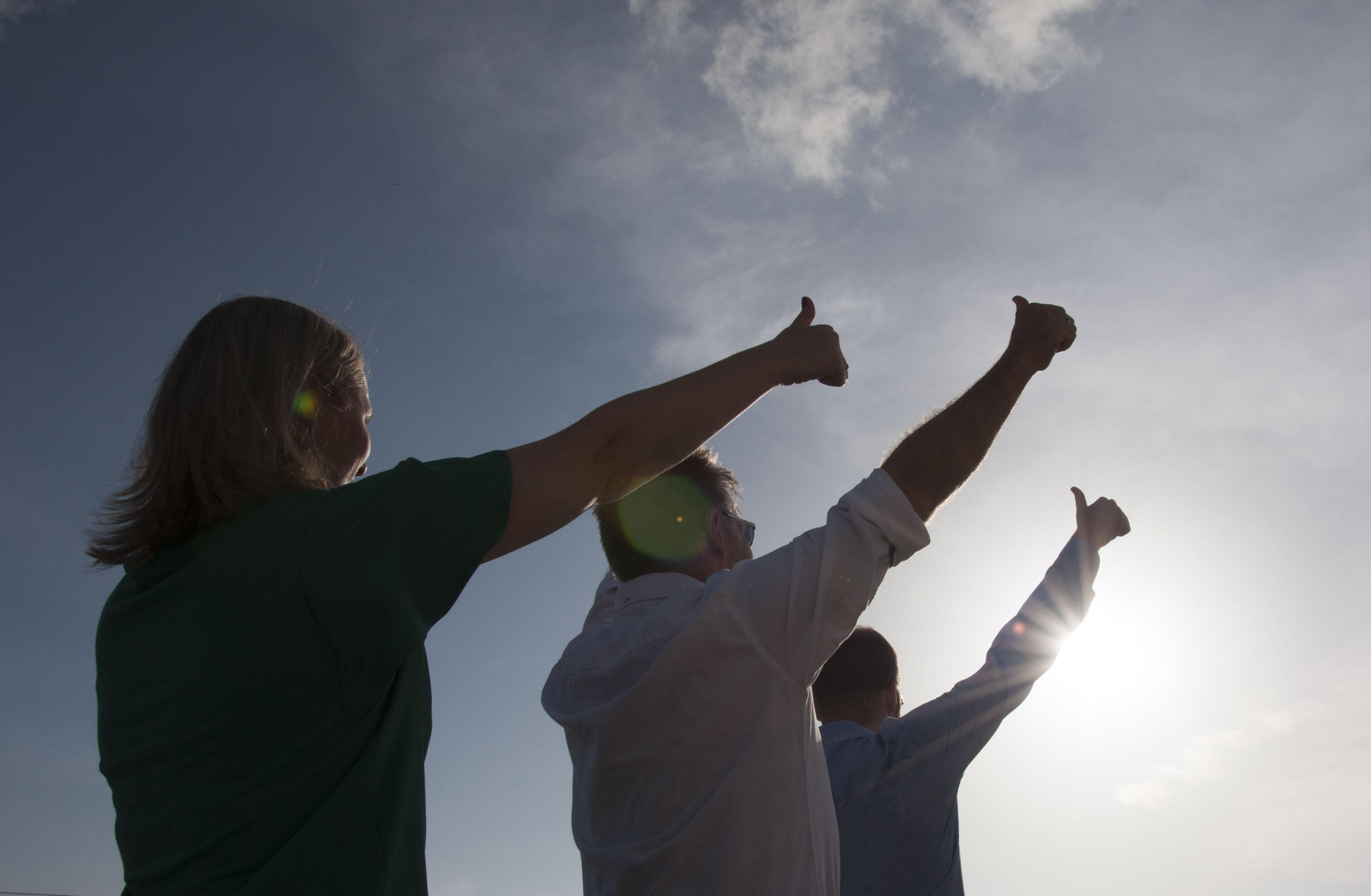 tre voksne mennesker som står ute med tommelen opp i lufta