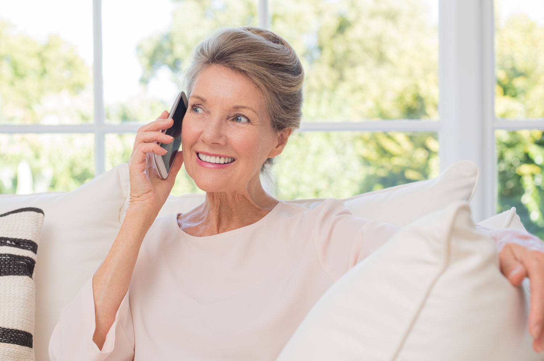 eldre dame som sitter påen sofa og snakker i telefonen